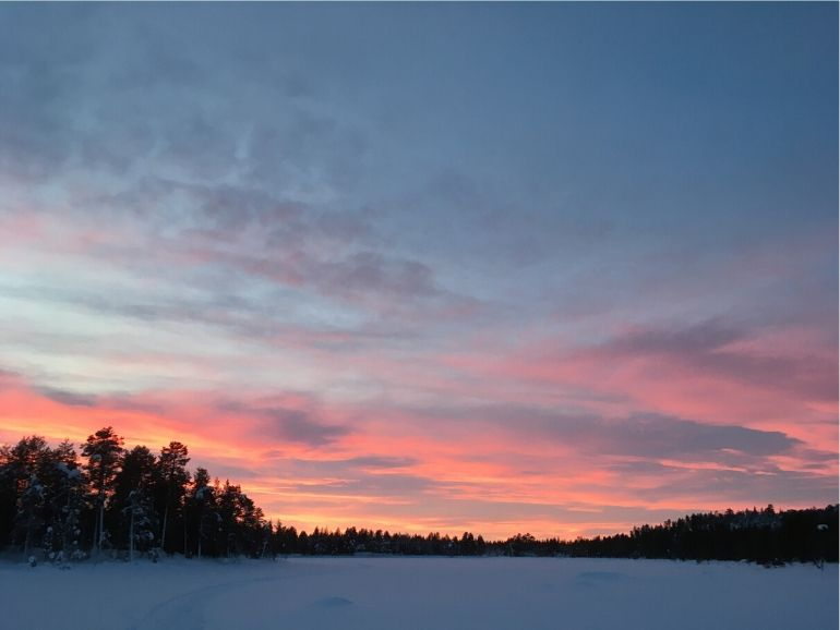 Reddish sky above a frozen lake.