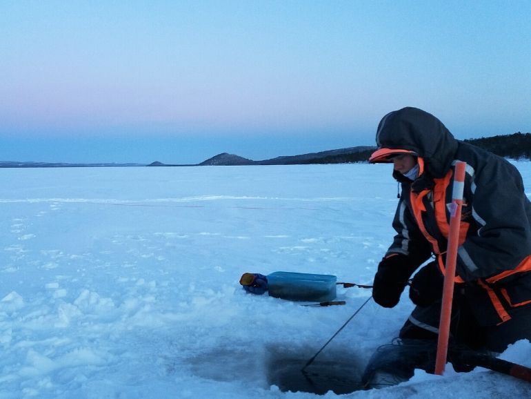 Terhi is taking out the fishing net under the ice.